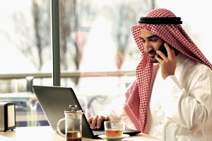Arab man working on the phone and a laptop in a coffee shop with a window in the background